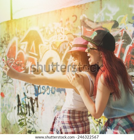 Two happy teenage girlfriends taking a selfie with smartphone outdoors on sunny summer day against graffiti wall. Square format, filter, filter applied, back light. - stock photo
