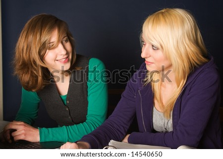 two happy teenager girls doing their study together - stock photo