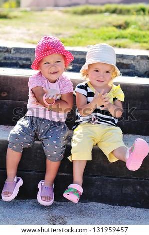 two happy toddler girls having fun outdoors - stock photo