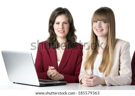 Two happy women blonde and brunette, sitting together in front of a laptop - stock photo