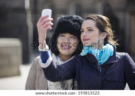 Two happy women, friends taking self portrait with their phone Camera Outdoors. Caucasian and Chinese friends taking photo with phone. - stock photo