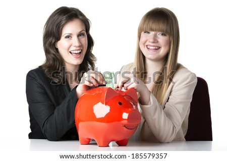 Two happy women sitting at a table and throwing 100 euro in a red piggy bank - stock photo