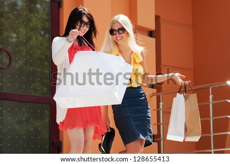 Two happy women with shopping bags on the steps - stock photo