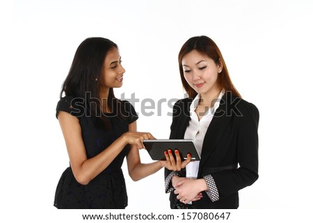 Two happy young Asian business women presenting; on a white background. - stock photo