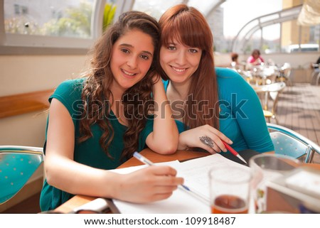 Two happy young beautiful women studying - stock photo