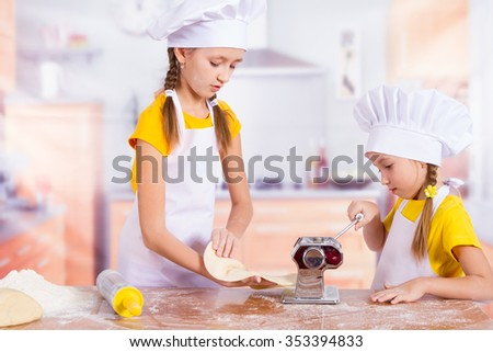 Two happy young chefs stretch the dough, - stock photo