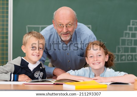 Two happy young children with their elderly male teacher in the classroom posing together in front of the blackboard smiling at the camera - stock photo