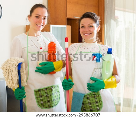 Two happy young cleaners woman cleaning room together - stock photo