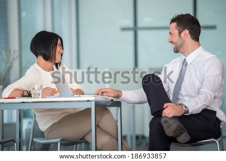 Two happy young coworkers talking in office - stock photo