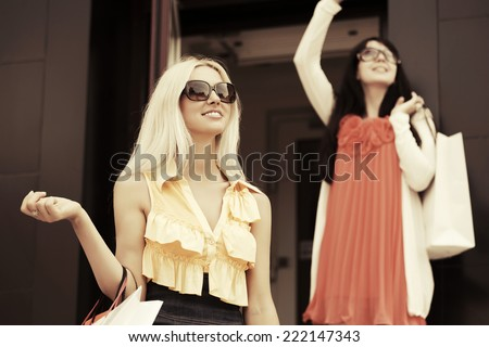 Two happy young fashion women with shopping bags - stock photo