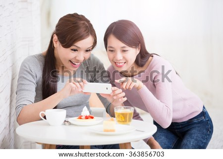 Two happy young female friends take picture by smart phone, with coffee cups and cakes in the living room at home, healthy lifestyle concept, asian beauty - stock photo