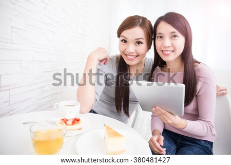 Two happy young female friends use digital tablet pc with tea, coffee and cakes, healthy lifestyle and tecnology concept, asian beauty - stock photo