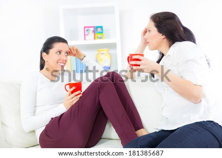Two happy young female friends with coffee cups conversing in the living room at home - stock photo
