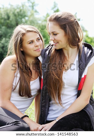 Two happy young girlfriends look at each other - stock photo