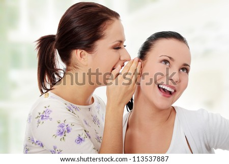 Two happy young girlfriends talking rummors - stock photo