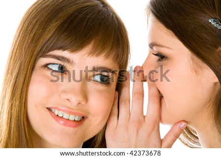 Two happy young girlfriends telling secret. Isolated on white background - stock photo