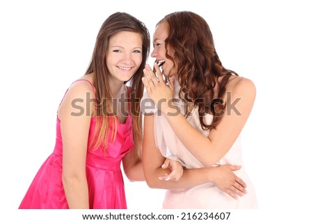 two happy young girlfriends whispering over white - stock photo