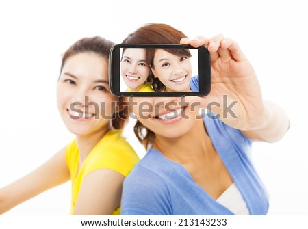 two happy young girls taking a selfie over white background - stock photo