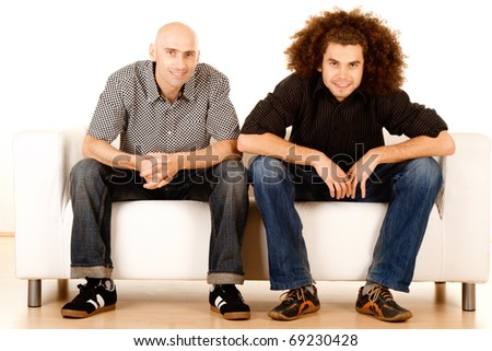Two happy young male friends relaxing on sofa or settee, white background. - stock photo