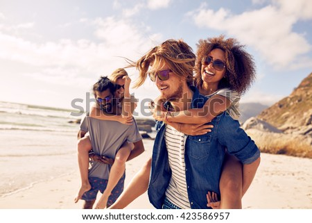 Two happy young men giving their girlfriends piggyback rides. Group of young people enjoying themselves during summertime at the beach. - stock photo