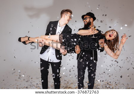 Two happy young men laughing and holding young woman with glass of champagne over white background - stock photo