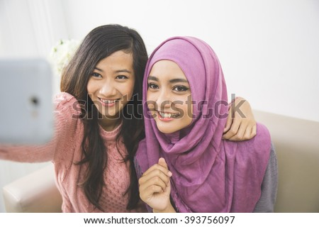 two happy young muslim woman take self portrait with handphone at home - stock photo