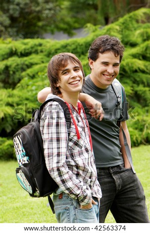 Two happy young students in park - stock photo