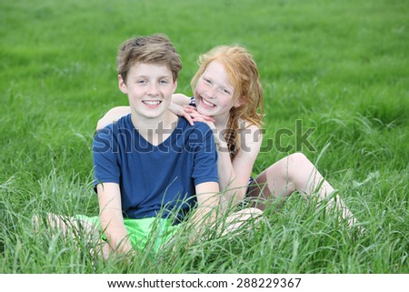Two happy young teenager sitting in a meadow - stock photo