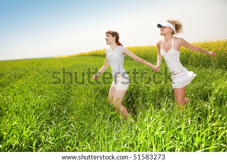 Two happy young women are running in a field - stock photo