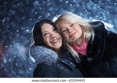 Two happy young women enjoying snow, closeup. - stock photo