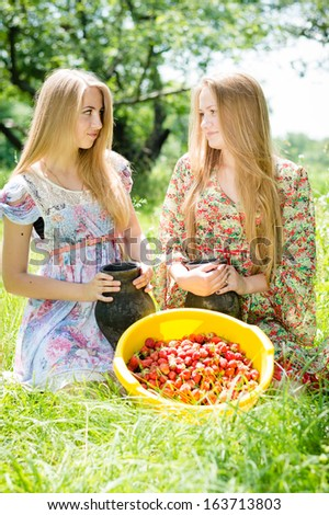 Two happy young women gathering strawberry on bright summer day outdoors background - stock photo