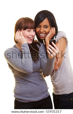 Two happy young women listening to music with a cell phone - stock photo