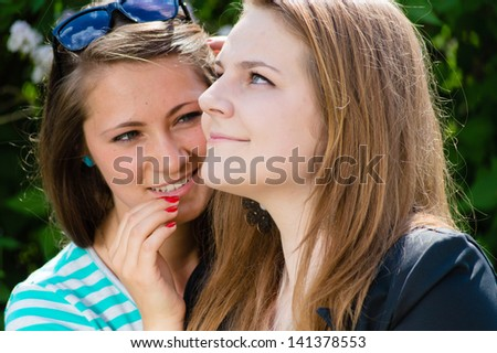 Two happy young women teen girl friends whispering secret on bright summer day outdoors - stock photo