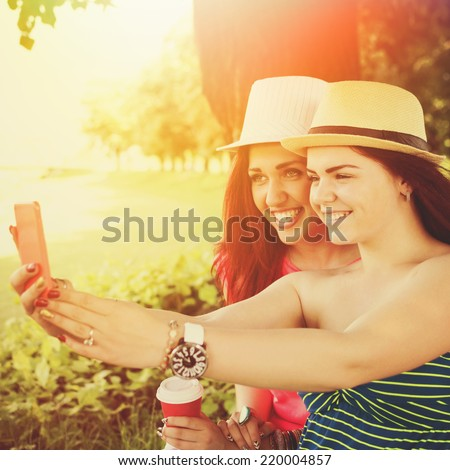 Two happy young women with hats taking a selfie in park. Two girlfriends sitting in park taking a self portrait with smartphone enjoying sunny day.  Square format. - stock photo