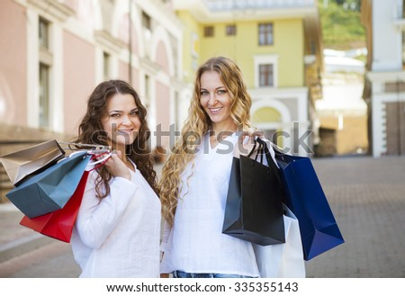 Two happy young women with shopping bags walking on the street - stock photo
