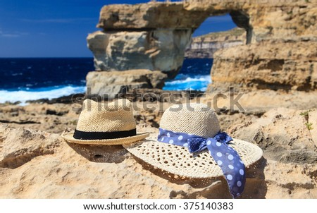two hats at Azure Window on Gozo island, vacation in Malta - stock photo