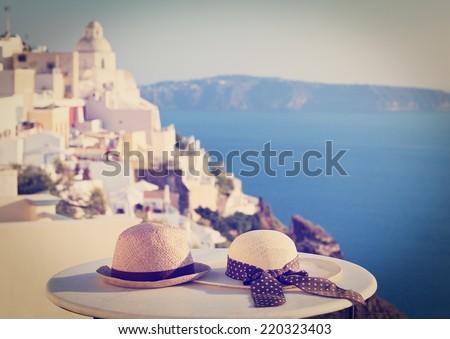 two hats on Santorini island, image of honeymoon and summer vacation - stock photo