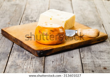 Two heads of cheese on wooden board and knife - stock photo