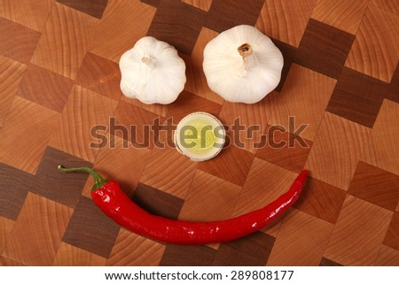 two heads of garlic, slice of a leek and chili pepper on a chopping board - stock photo