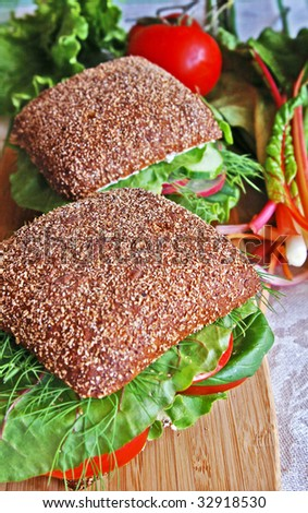 Two healthy rye bread sandwiches with fresh radish, cucumber, tomatoes, green vegetables and herbs on a wooden kitchen board, blur background, vertical - stock photo