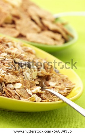 Two heaps of breakfast cereal in plates close-up on green cloth. - stock photo