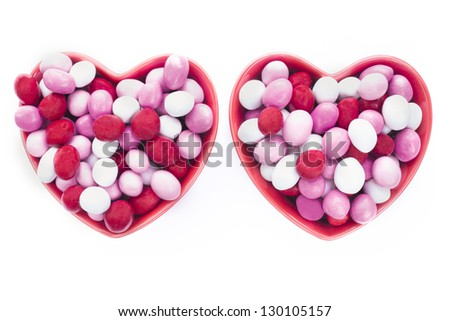 Two heart shaped dishes full of candy-coated chocolates isolated on white - stock photo
