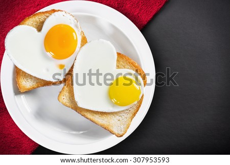 Two heart-shaped fried eggs and fried toast  on a plate - stock photo