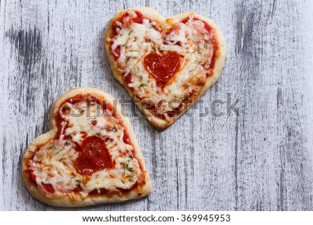 Two heart shaped pizzas with copy space / Valentine heart pizza top down view - stock photo