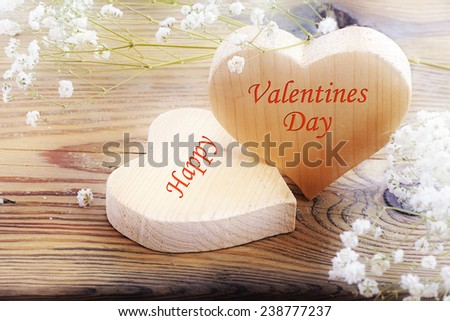 two heart shapes of wood on old wooden background,  message happy valentines day - stock photo