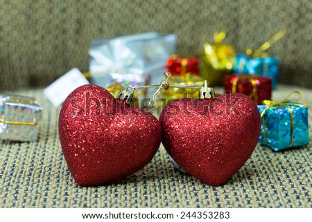 Two hearts binding together with golden rope among gifts - stock photo