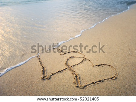 two hearts drawn in beach in sunset - stock photo