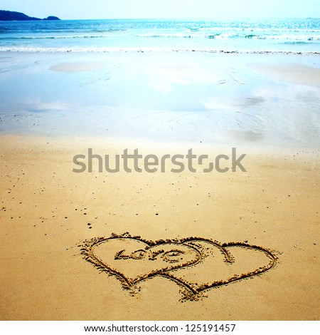 Two hearts drawn in the sand on the beach. Romantic design element. - stock photo