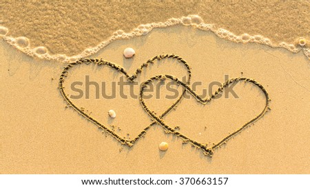Two hearts drawn on the sand beach with the soft wave. Honeymoon concept. - stock photo