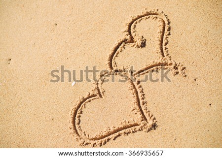 Two hearts drawn on the sand of a beach background - stock photo